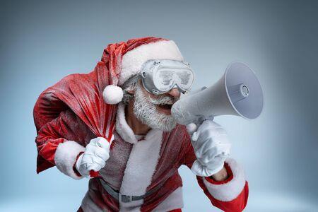 Mature Santa Claus with sack speaking at megaphone
