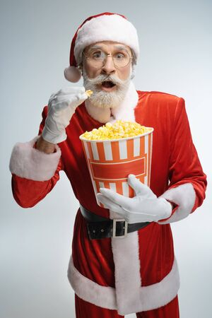 Excited mature aged Santa Claus eating popcorn Stock Photo