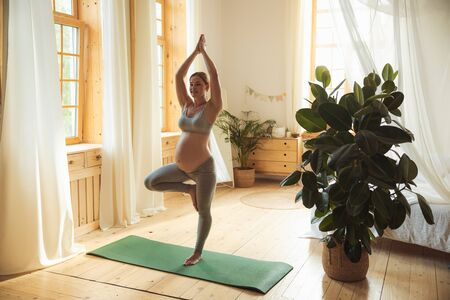 Beautiful pregnant woman doing tree pose or vrishasana