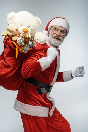 Elderly Santa Claus holding sack with presents Stock Photo