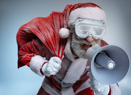 Elderly Santa Claus with sack speaking at megaphone Stok Fotoğraf
