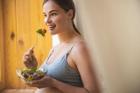 Joyful young woman eating fresh vegetable salad Stock Photo