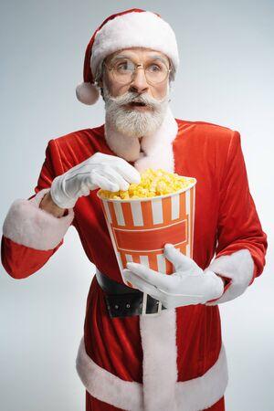 Elderly Santa Claus holding popcorn bucket in hands