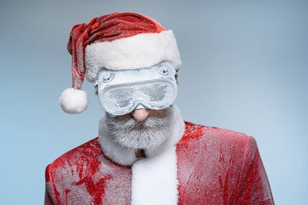 Elderly Santa Claus standing in costume and protective glasses