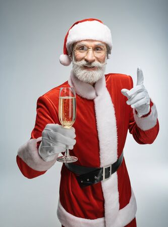 Santa Claus with glass of champagne in hand Standard-Bild