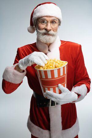 Santa Claus with popcorn bucket in hands