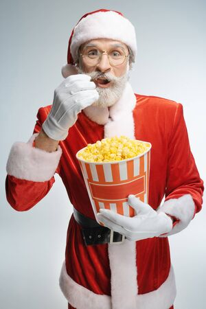 Senior Santa Claus eating popcorn from bucket