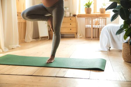 Pregnant young lady practicing yoga at home