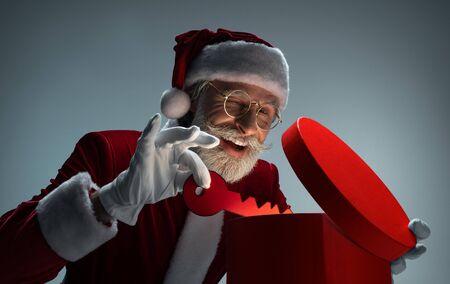 Elderly Santa Claus packing key in gift box