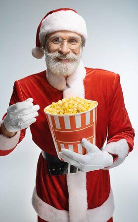 Mature Santa Claus with popcorn bucket in hands