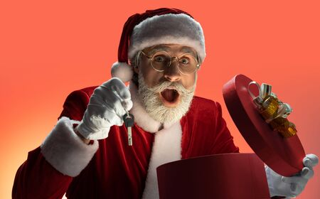 Elderly Santa Claus holding car keys and gift box