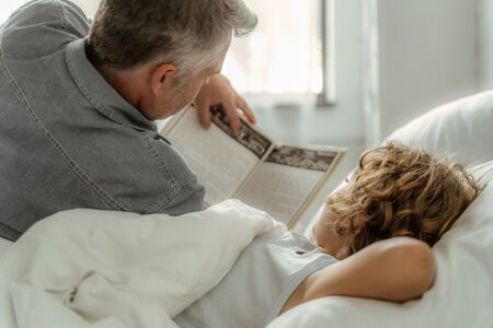 Father reading book with son in morning