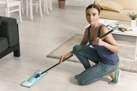 Calm woman using mop at home stock photo