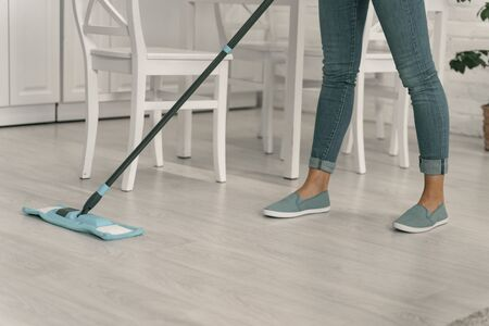Woman tiding up floor with broom stock photo