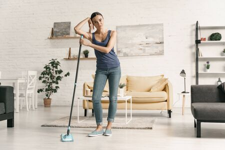 Tired female with mop at home stock photo