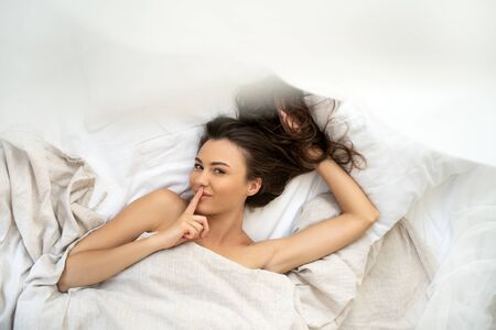 Charming young woman lying in bed and pressing finger to her lips