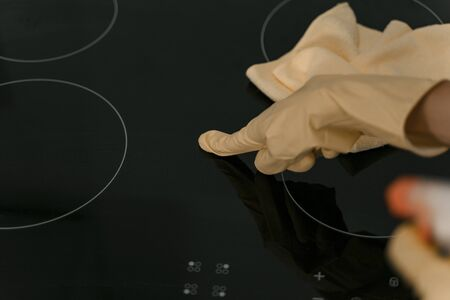 Housewife tiding up cooking surface stock photo