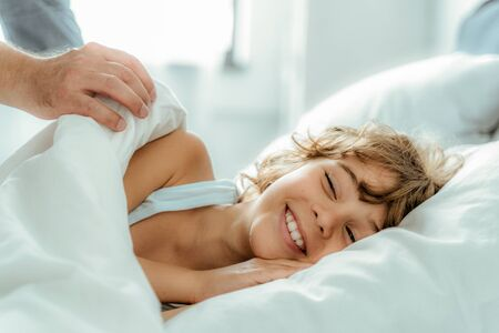 Father awakening his happy kid at morning Stock Photo