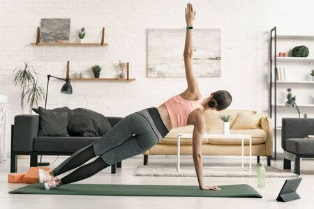 Female practicing side plank at home stock photo Banco de Imagens