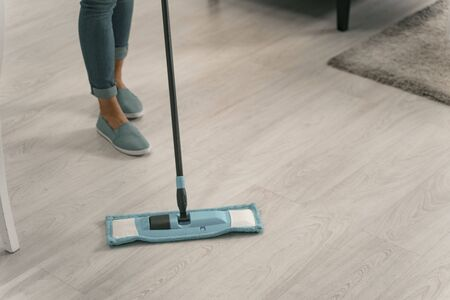 Woman wiping wooden floor with mop stock photo