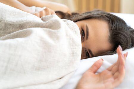 Attractive young woman hiding face under blanket Banco de Imagens