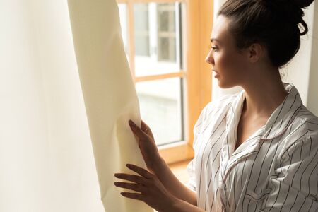 Attractive young woman looking out of the window