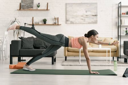 Woman in extended plank at home stock photo