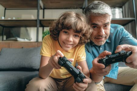 Mature father with son playing in video games