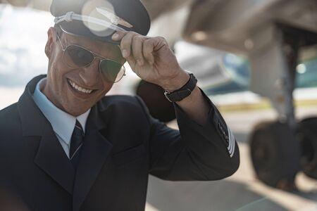 Uomo bello felice in uniforme che posa per la macchina fotografica Archivio Fotografico