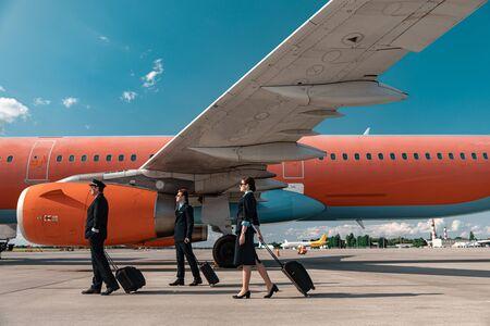 Caucasian pilots and flight attendant walking in airport Banco de Imagens