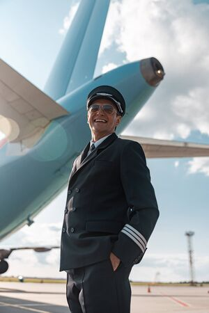 Handsome happy pilot resting outdoors in airport Stock Photo