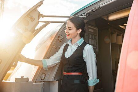 Beautiful female flight attendant is on duty on board