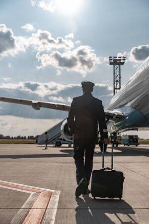 Volwassen piloot haast zich voor de vlucht op de luchthaven Stockfoto