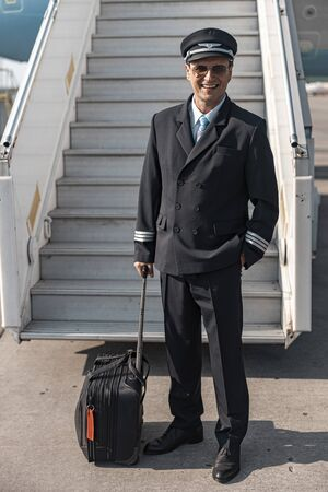 Handsome adult pilot with his suitcase standing near plane ladder