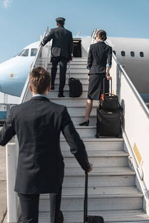 Crew of aiplane with suitcases entering plane board before flight stock photo. Airways concept