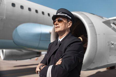 Handsome pilot in uniform posing for camera