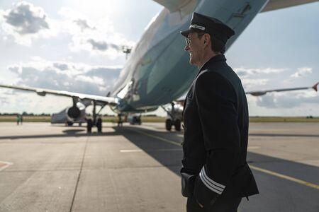 Happy cheerful pilot in costume standing near airplane