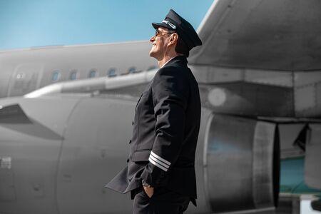 Adult man in cap looking in sky in airport