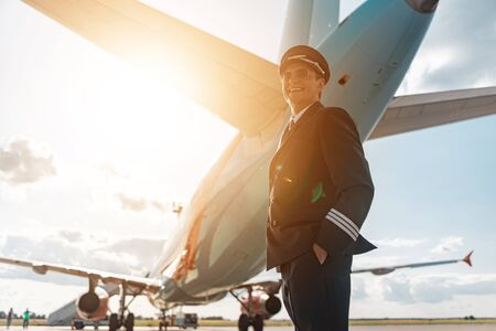 Handsome happy pilot in sunglasses standing under airplane in airport