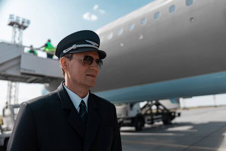 Handsome male pilot in uniform posing for camera