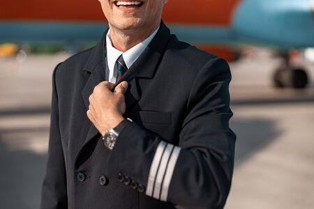 Caucasian pilot straightening his tie before flight Stock Photo