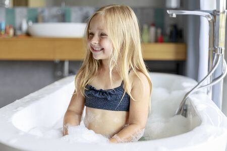 Happy girl sitting in the bath with foam Imagens