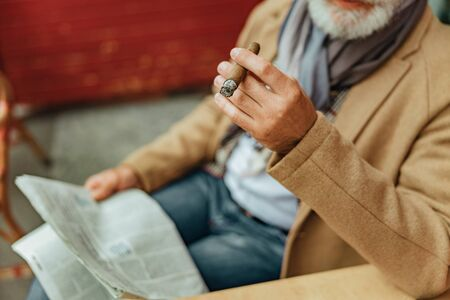 Senior man holding Cuban cigar and newspaper Stok Fotoğraf