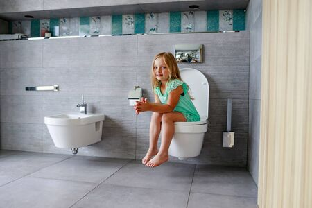 Cute little girl in toilet at home