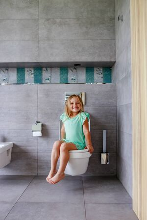 Smiling girl sitting on a toilet in bathroom Stockfoto