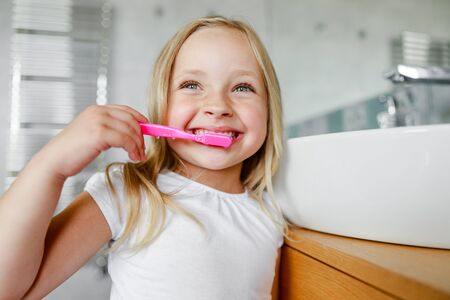 Smiling cute girl is holding a toothbrush Stock Photo