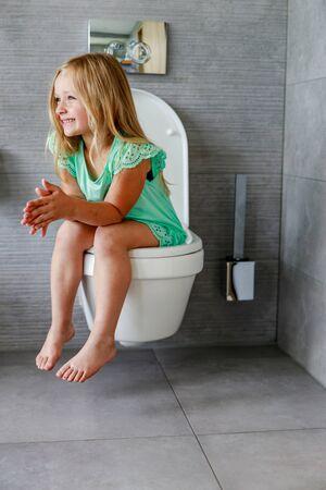 Feliz niña en el inodoro en el baño