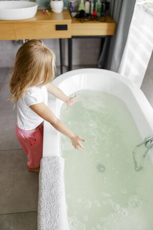 Girl in pajamas standing near the bath