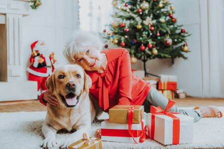 Happy senior woman is sitting with pet on floor