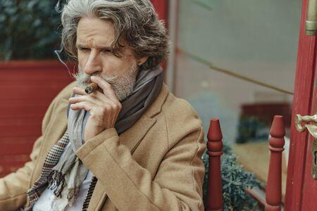 Handsome senior man smoking cigar on the street